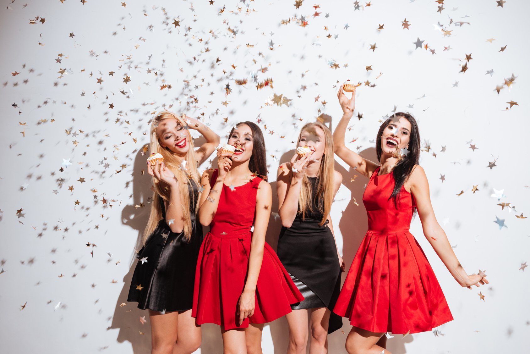 Four cheerful beautiful young women dancing and eating cupcakes on the party over white background